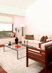 Un intérieur rangé, une table en verre, une couleur d'ensemble claire avec quelques touches colorées
