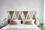 Décoration de chambre de style scandinave avec tête de lit bois et gris en triangles.